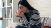 conforto : smile Asian woman drinking hot chocolate and keeping warm and looking outside autumn view on the sofa in the living room at home Vídeos