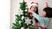 parıldıyor : beautiful Asian mother and daughter decorating Christmas tree and having fun.