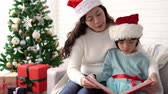 presente de natal : Pretty young Asian mom reading a book to her cute daughter near Christmas tree indoors at home. Merry Christmas and Happy Holidays!