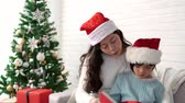 fadas : little cute Asian girl listening to a Christmas story from her mother reading a book in the living room at home. Stock Footage