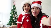 уютный : mom and her daughter girl making a blessing live video for Christmas and new year in the living room at home.