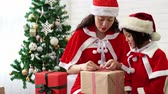 piscar : Santa mother and her kids packing the gifts box together