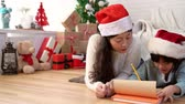parıldıyor : cute Asian little kid girl and her mother write the letter together to Santa Claus lying down on the floor of the living room at home. Christmas winter holiday concept. Stok Video