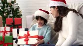wróżka : little cute Asian girl feels surprised face expression after she received and open the Christmas gift box from her mother sitting on sofa at home. Wideo