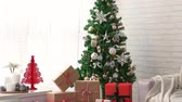 cópia : decorated Christmas room with beautiful fir tree, many gift box underneath in the living room.