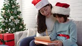 parıldıyor : Merry Christmas! Cute Asian little child girl and her mother write the letter together to Santa Claus in the living room at home.