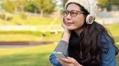 canção : Asia girl student enjoys listening music with the smartphone in a park sitting on the grass in a park. Vídeos