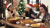 jantar : asia friends sitting around a wooden table and enjoying Christmas dinner together at home