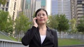 japonês : Businesswoman talking on the mobile phone and walking in the central park