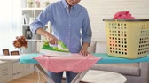 lavanderia : beautiful happy housewife sort out family clean clothing with iron on ironing board in living room and looking at camera smiling. Vídeos