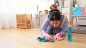 trapo : Housewife kneeling on the floor with detergent and rag carefully wipe the floor woman was surprised that the floor is still very dirty at home in the living room for end of year cleaning