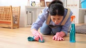 diário : Woman with a cleaning glove holding a rag Kneeling on the floor struggling to wipe the dirty floor to make the home cleaner