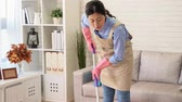 limpeza : Happy Young Woman Cleaning The Hardwood Floor With Mop In Living Room at home during spring clean