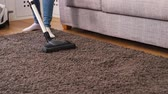 diário : Pan shot of young woman using a vacuum cleaner while cleaning carpet in the house during daily clean housework and household concept.