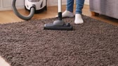 não higiênico : Woman using vacuum cleaner on carpet at home in the living room during spring clean