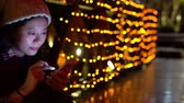 japonês : beautiful girl using smartphone texting and illumination light on the background at evening.