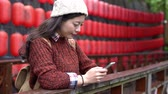 desgaste : young girl traveling to japan using mobile phone texting while japanese red lantern on the background