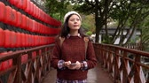 japonês : pretty japanese girl walking on wooden bridge enjoy the outdoor view and stop texting message while red lantern on the background. japanese text meaning hot springs on the lantern.