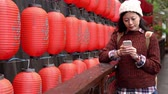 desgaste : asian woman walking and stop on bridge texting message while red lantern on the background. japanese text meaning hot springs on the lantern.