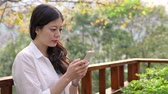 japonês : young woman working on holiday outdoor with smartphone texting message.