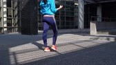 witalność : Young woman doing some warm up before run. Runner leaning on city relaxing her calf muscles. Wideo