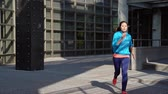 únor : slow motion of young woman jogger starting run at the city building background