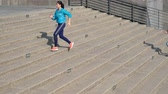 dostihy : two girl jogger tracing together on city concrete stair. healthy lifestyle sports woman running up on stone stairs with the great sunny weather.
