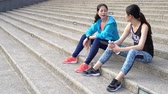 dostihy : two girl friends jogger having the conversation and drink water after running sitting on city concrete stair.