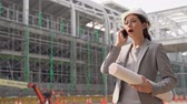 кран : female engineer business in suit and helmet talking on a mobile phone holding a blueprint paper construction on the background. Стоковые видеозаписи