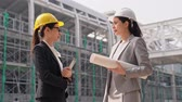 built structure : Professional Asian female engineers are shaking hands and smiling. businesswoman standing near the building and looking at each other with trust.