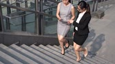 discussão : Two Asian women talking about business with holding digital tablet while walking up stairs outside of office building