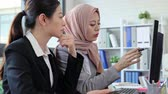 discutir : professional Asian businesswoman and Muslim businesswoman working together discuss with computer for year plan in startup office. Vídeos