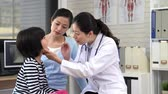 gripe : mom take her little girl having throat examination by pediatrician using light pen and wood stick.