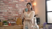 bem : slow motion of woman in kitchen smile at the camera. She drinks some hot tea and turned around looking at the camera. Vídeos