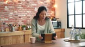 bem : Slow motion of woman preparing to cook. She is dancing and browsing the digital recipe by using a tablet.