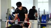 ginásio : Asian strong male coach helps the female students to lift the dumbbells slowly in the gym.