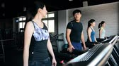 satisfy : Young Asian girl exercises in the gym and chatting with a man at the same time.