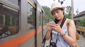 получать : Slow motion of the girl tapping the cell phone beside the train. She is connecting her friend. Стоковые видеозаписи