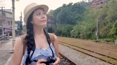 kolej : Asian woman walking along the railway. She is coming for taking pictures. She is a photographer.