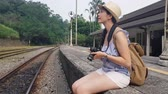 trilho : Asian girl sitting on the platform stairs beside the railroads and looks around the view beside her.