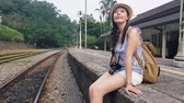 kolej : Slow motion of the childlike girl sitting on the stairs beside the old Japanese railway station platform Wideo