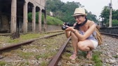 um : Asian girl kneels down and takes a picture on the railway.