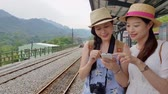 kolej : Two Asian female standing beside the train rail and looking to the smartphone to plan where to go later. Wideo