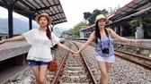 trilho : Slow motion of two Asian girls walking on the train rail. They hold hand in hand to keep on balance.