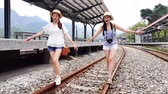trilho : Two Asian girls walking on the railroad. Slow motion concept.