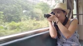 trilho : Young Asian girl holding the camera and taking a photo of the natural sight outside of the train.