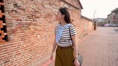 A quick motion of the Asian woman walking passed the ancient alley in Lukang. She is looking around to see the special old walls. Stock Footage