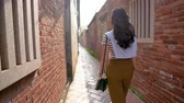 chodec : Asian female pedestrian carrying a black bag is walking passed the ancient old alley.