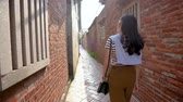 ruína : Asian woman walking through the ancient street and turned around to look at the camera. Vídeos