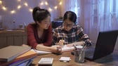 Group of asian chinese female roommates in college dormitory solve problem on textbook together at late night.